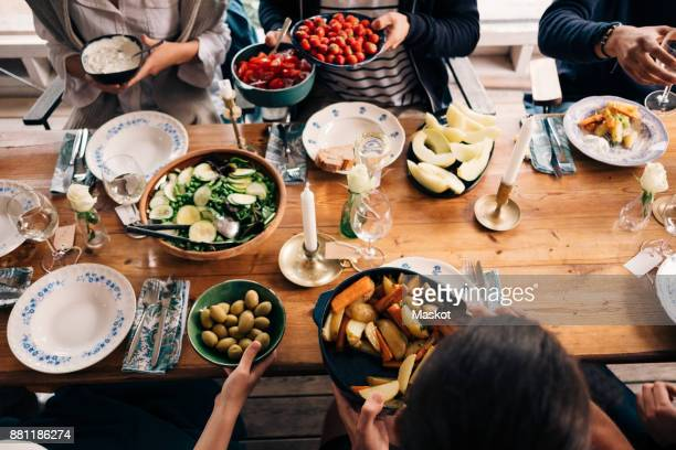 High angle view of men and women having food together in cottage