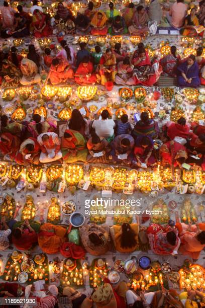 high angle view of men and women sitting side by side while praying - large group of people stock pictures, royalty-free photos & images