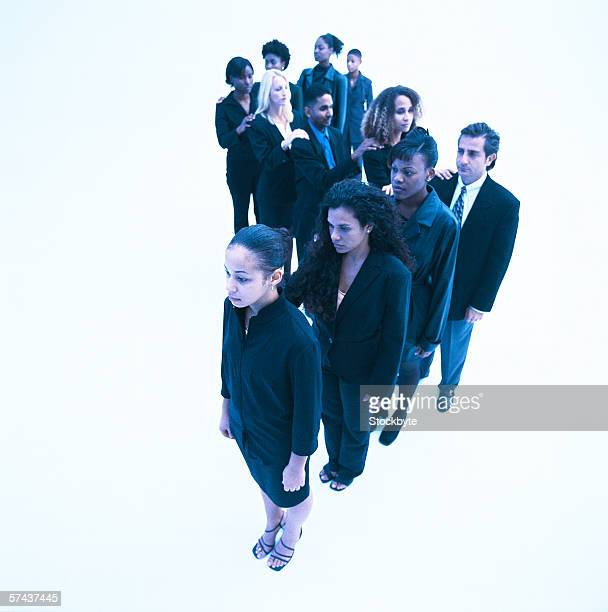 high angle view of men and women standing in a winding line at arms length