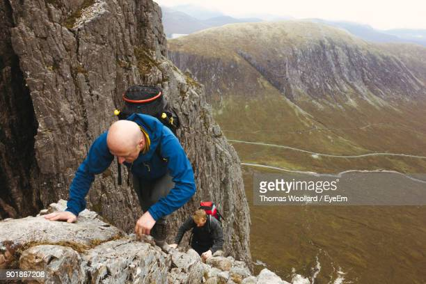 High Angle View Of Men Climbing On Rocky Mountain