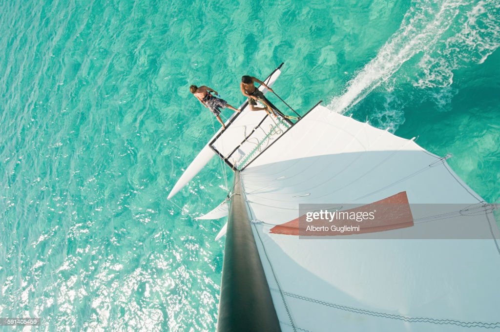 High angle view of men hoisting rigging on sailboat : Stock Photo