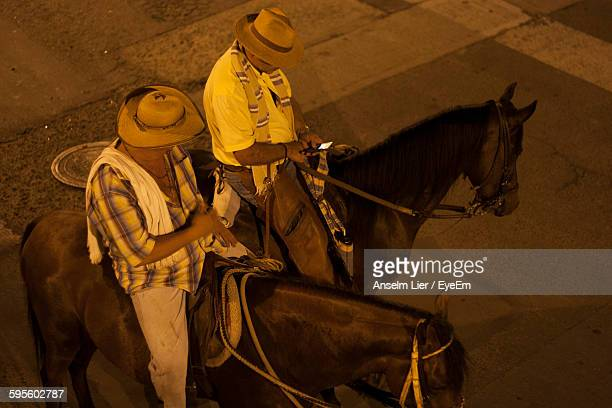 High Angle View Of Men On Horses At Night