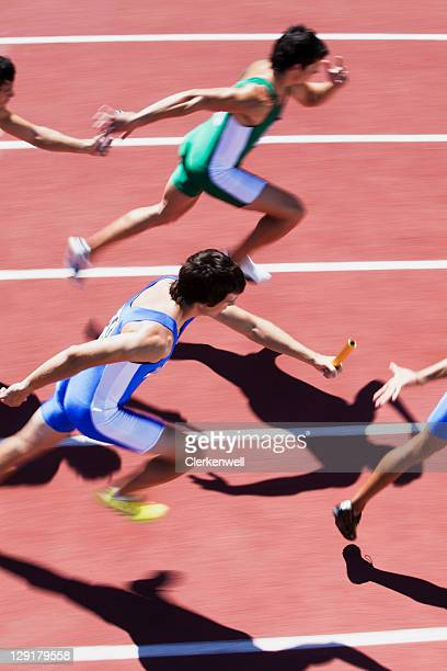 High angle view of men passing relay baton