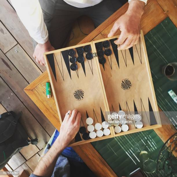 high angle view of men playing backgammon - backgammon stock pictures, royalty-free photos & images