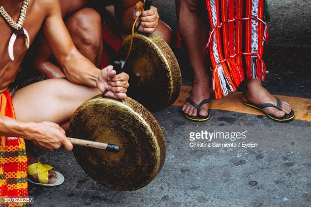 high angle view of men playing gong on road - gong stock photos and pictures