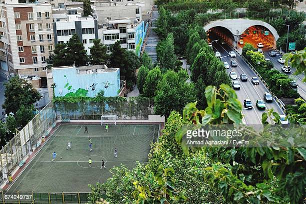 high angle view of men playing on soccer field in city - football bulge stock photos and pictures
