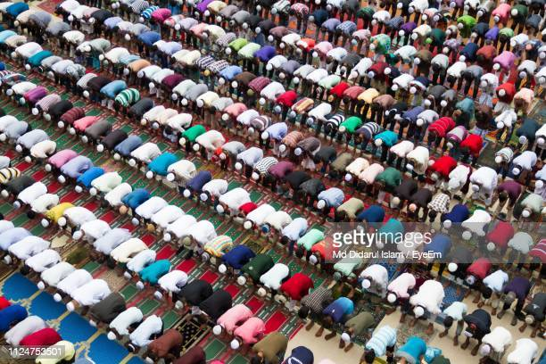 high angle view of men praying in mosque - mosque stock pictures, royalty-free photos & images