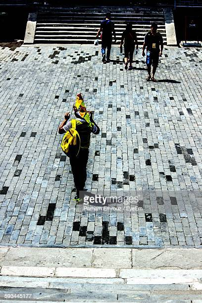 high angle view of men walking on footpath - parham emrouz stock pictures, royalty-free photos & images
