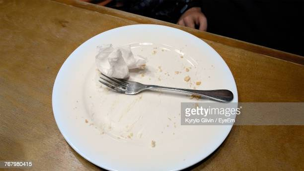 High Angle View Of Messy Plate With Fork And Tissue Paper On Table