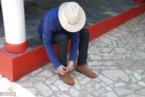 High Angle View Of Mid Adult Man Tying Shoelace While Sitting Outdoors