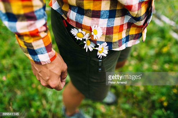 High angle view of mid adult man wearing checked shirt with daisies in shorts pocket, Moraine lake, Banff National Park, Alberta Canada