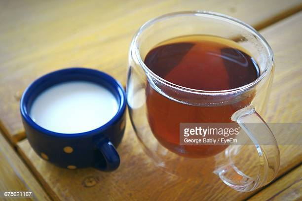 High Angle View Of Milk And Tea On Wooden Table