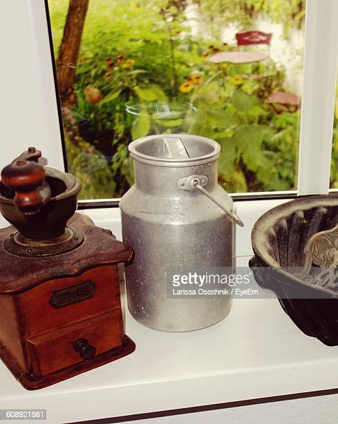 High Angle View Of Milk Canister And Grinder On Window Sill