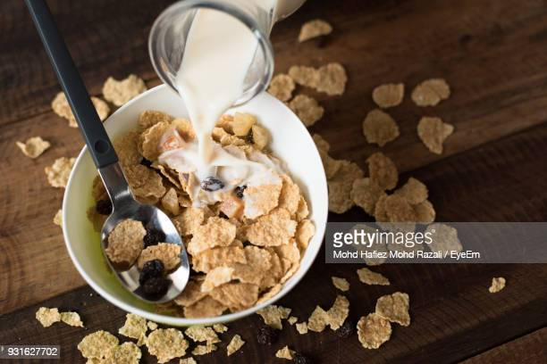High Angle View Of Milk Pouring From Jug In Bowl Of Breakfast Cereal On Wooden Table