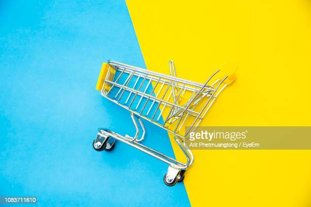 high angle view of miniature shopping cart against blue background - shopping cart stock pictures, royalty-free photos & images