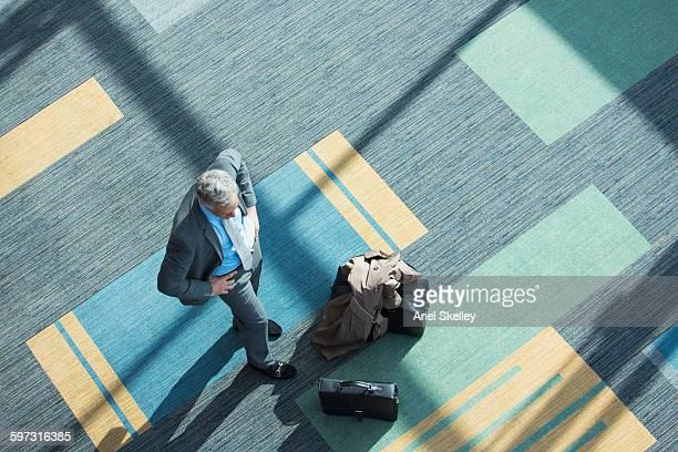 High angle view of mixed race businessman in airport
