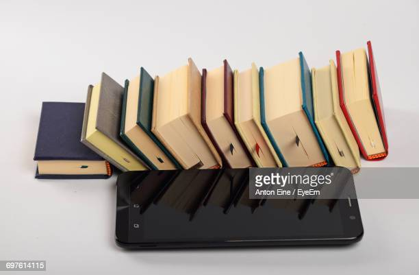 High Angle View Of Mobile Phone By Books On White Background