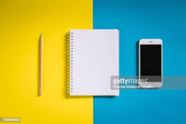 high angle view of mobile phone with note pad and pencil over colored background - personal organiser stock photos and pictures