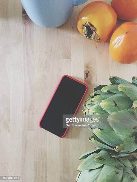 High Angle View Of Mobile Phone With Persimmon And Artichoke On Table