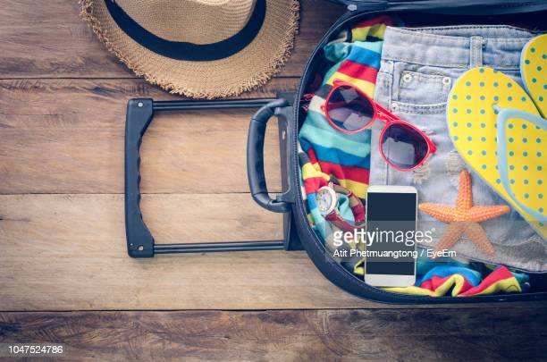 High Angle View Of Mobile Phone With Suitcase On Table