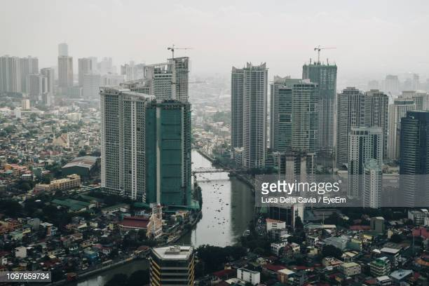 high angle view of modern buildings in city against sky - manila philippines stock pictures, royalty-free photos & images