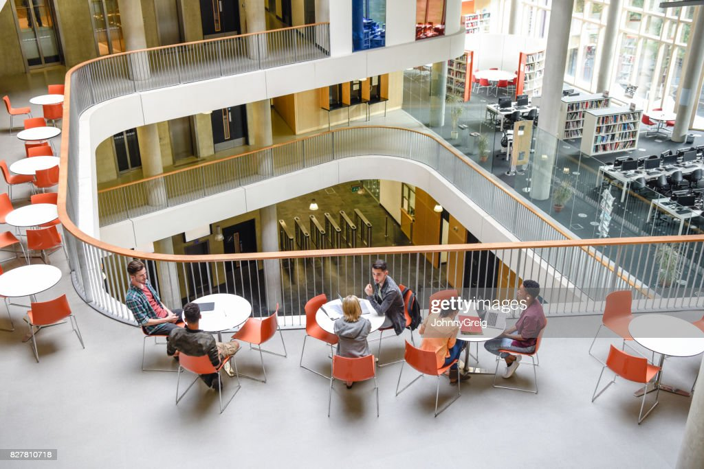 High angle view of modern college interior, students sitting around tables : Stock Photo