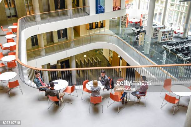 High angle view of modern college interior, students sitting around tables