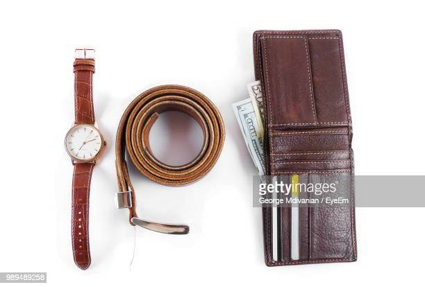 High Angle View Of Money With Belt And Watch Over White Background