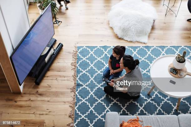 high angle view of mother and daughter watching television while sitting on floor at home - mirar un objeto fotografías e imágenes de stock