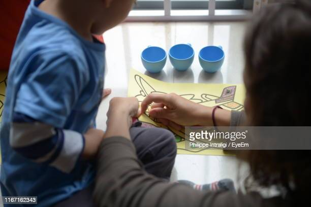 high angle view of mother and son coloring on table at home - family with one child stock pictures, royalty-free photos & images