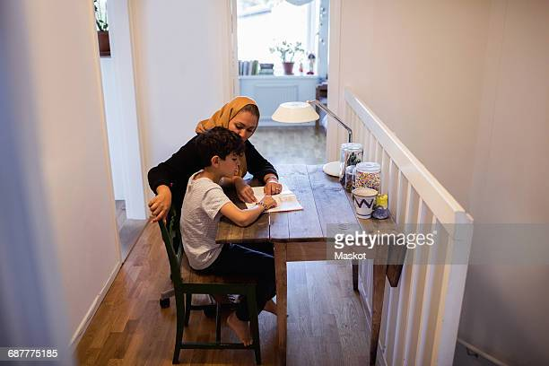 High angle view of mother and son reading book at home