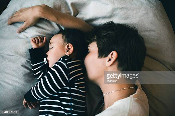 High angle view of mother and toddler sleeping on bed at home