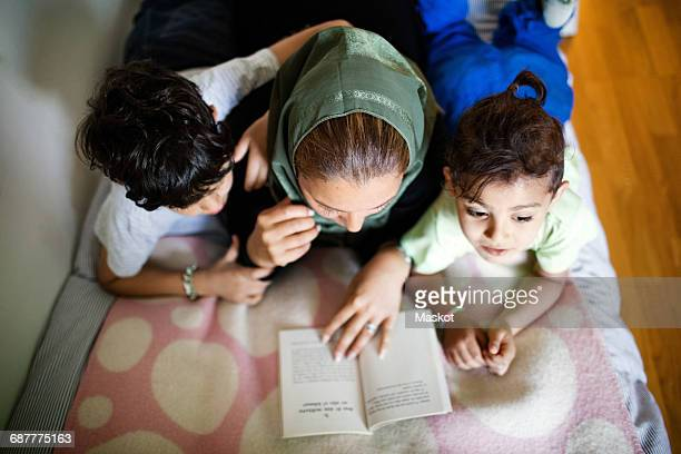 High angle view of mother reading book to boys while lying on bed at home