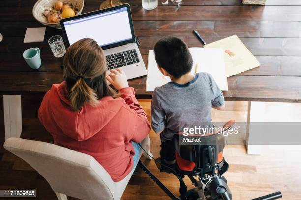 high angle view of mother with autistic son watching video on laptop while sitting at home - differing abilities fotografías e imágenes de stock