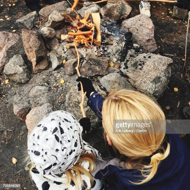 High Angle View Of Mother With Daughter Roasting Sausages Over Campfire
