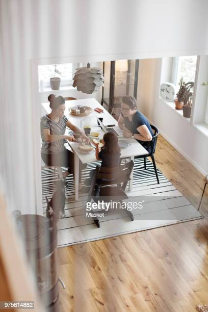 high angle view of mothers talking to daughter having breakfast at dining table - dog eats out girl stock pictures, royalty-free photos & images