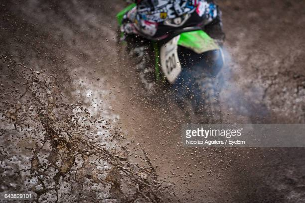 High Angle View Of Motocross Rider Splashing Mud