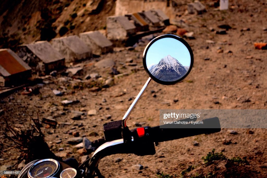 High Angle View Of Mountain Reflecting On Motorcycle Mirror At Dirt Road : Stock Photo