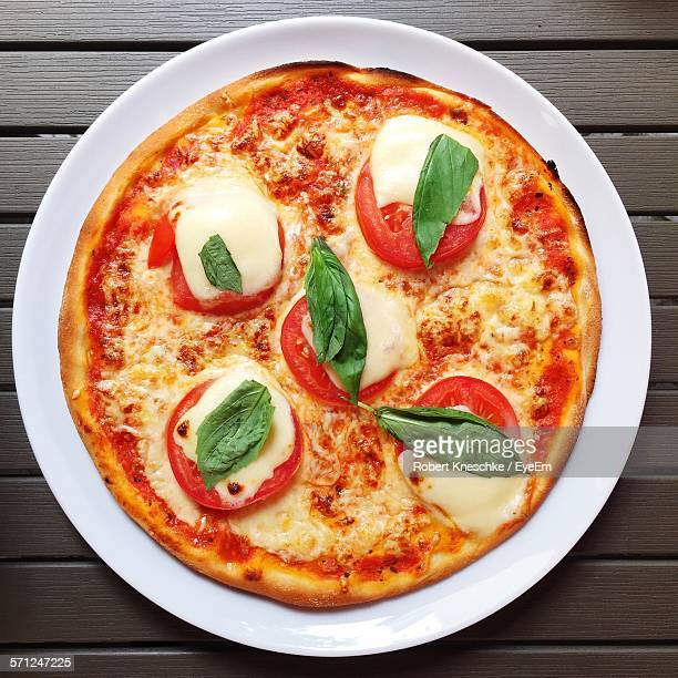 High Angle View Of Mozzarella Cheese On Pizza Served In Plate On Table