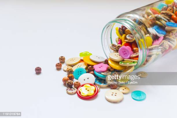high angle view of multi colored buttons in jar on white background - knoop naaigerei stockfoto's en -beelden