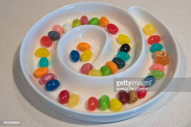 high angle view of multi colored candies in spiral plate - ignatius tan stock photos and pictures