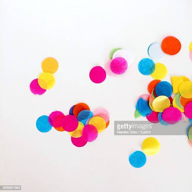 high angle view of multi colored confetti against white background - confetti stock pictures, royalty-free photos & images