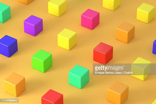 high angle view of multi colored cubes on yellow background - 立方体 ストックフォトと画像