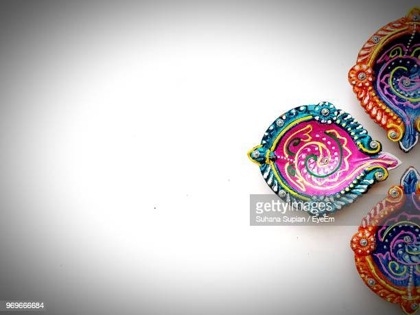high angle view of multi colored diya on white background - diwali celebration stock photos and pictures