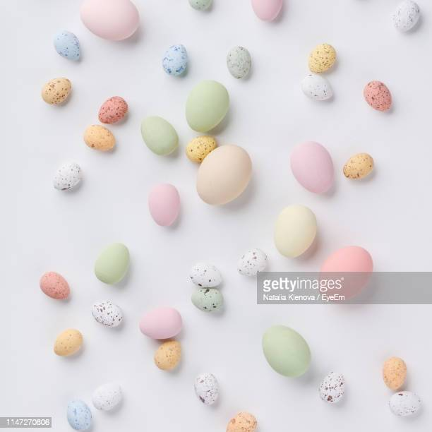 high angle view of multi colored eggs on table - easter candy stock pictures, royalty-free photos & images