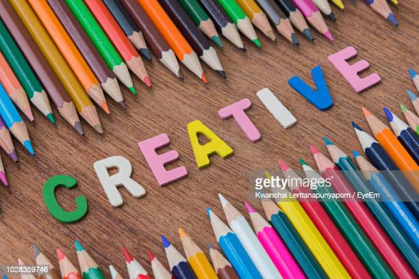 high angle view of multi colored pencils by text on floor - westers schrift stockfoto's en -beelden