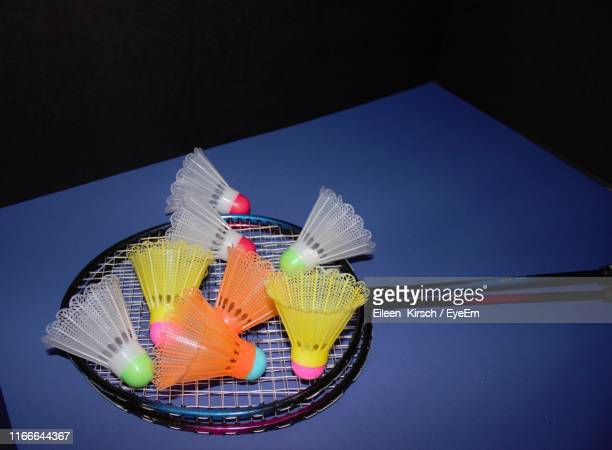 high angle view of multi colored shuttlecocks and rackets on table against black background - eileen kirsch stock pictures, royalty-free photos & images