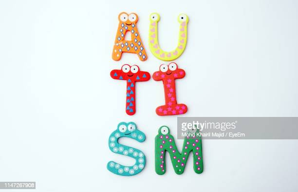 high angle view of multi colored text with anthropomorphic face against white background - autism awareness stock pictures, royalty-free photos & images