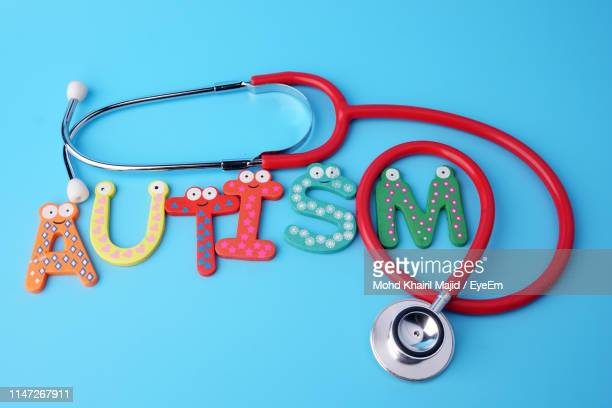 high angle view of multi colored text with stethoscope against blue background - autism awareness stock pictures, royalty-free photos & images