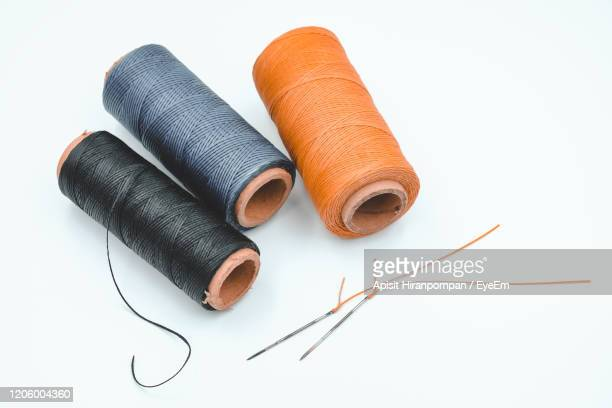 high angle view of multi colored thread and needles on white background - sewing stock pictures, royalty-free photos & images
